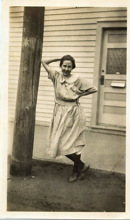 Emma, quite saucily leaning against a pole with one hand behind her head.