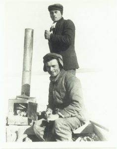 Oscar Huettner (standing) and Brother Alfred (sitting) ona a raft with a wood stove beside them