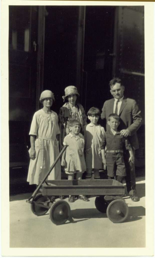 From the left: Grandma Klein, Emma, Millie, Helen, Oscar Sr. and Oscar Jr. with a wagon in front of them.
